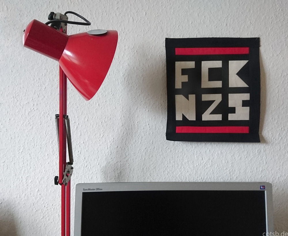 Patchwork an de Wand gepinnt, daneben eine rote Lampe